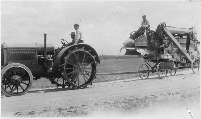 This image has an empty alt attribute; its file name is 800px-Tractor_pulling_combine_along_the_road_-_NARA_-_285480.jpg